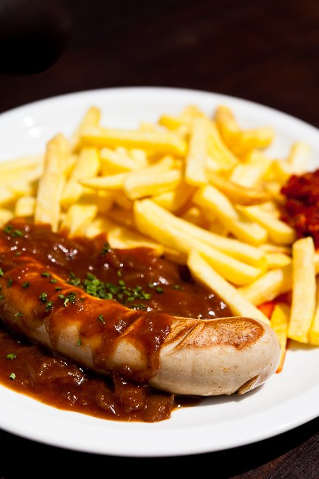 A plate of sausage, chips and gravy on a white plate