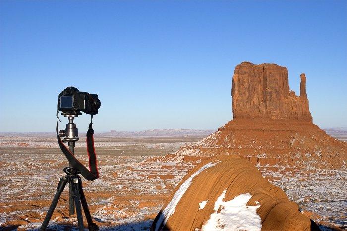 A DSLR camera on a tripod pointed at a rocky barren landscape