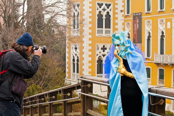 A man taking a photo of a person in an extravagant carnival costume during a travel photography trip