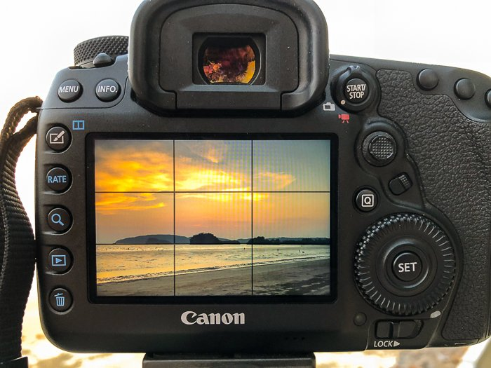 A canon DSLR with a beautiful sunset seascape onscreen