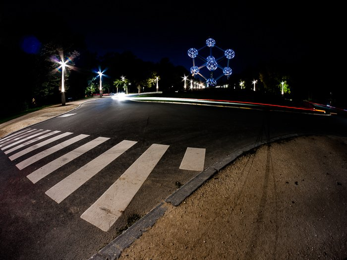 An urban night scene with red light trails caught around a roundabout in Brussels