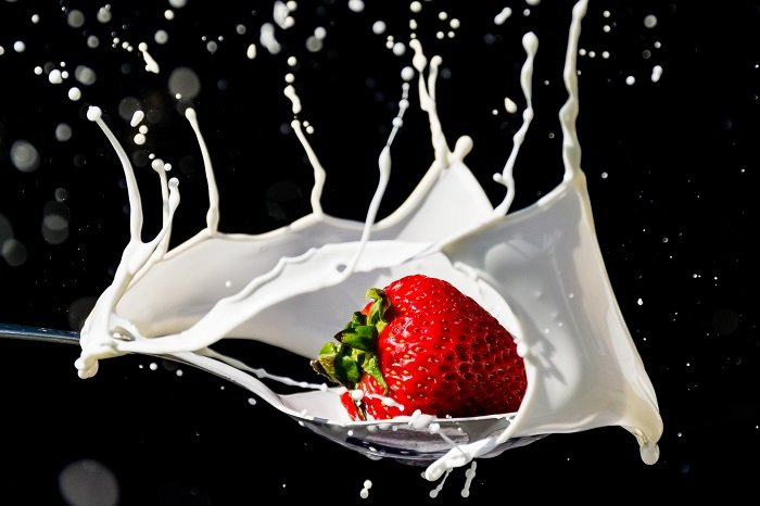 A slice of fruit photographed as it drops into water and creates a splash