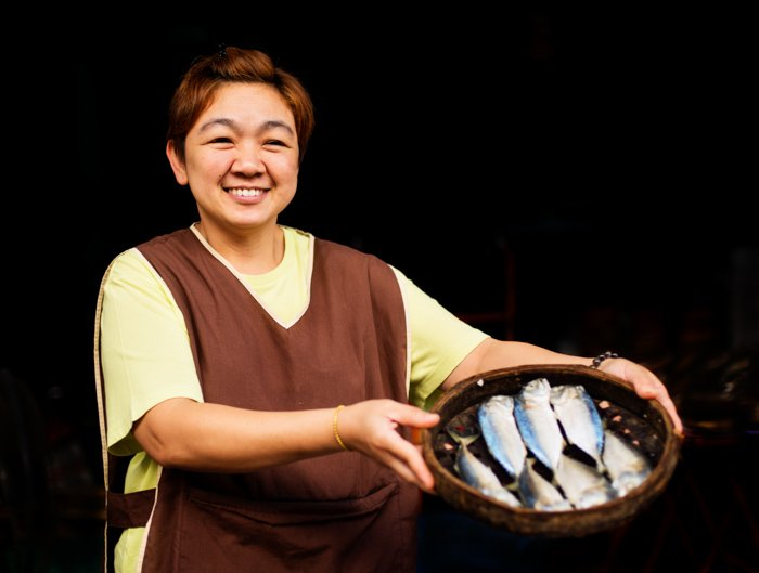 A smiling woman poses with a basket of fish for portrait against a dark background