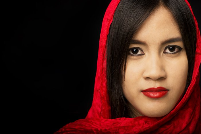 An Asian woman with red scarf poses for portrait against a dark background - how to create a black background for photography portraits.