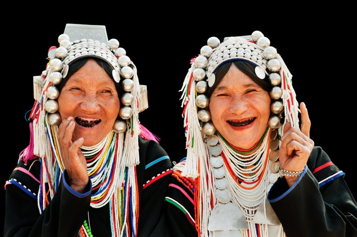Portrait of two Akha hill tribe women in northern Thailand, posing against a black background for photography.