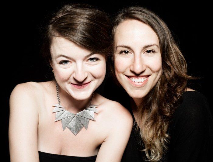 A studio portrait of two girls against a black backdrop