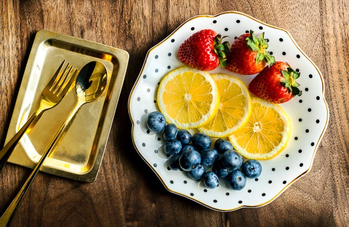 Overhead shot of a luxurious plate of fruits with golden cutlery to be used as photography props for a boudoir shoot