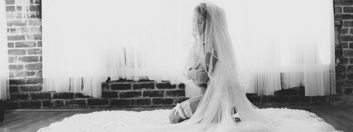 Ethereal black and white boudoir photography shot of a girl in bridal wear sitting on a rug