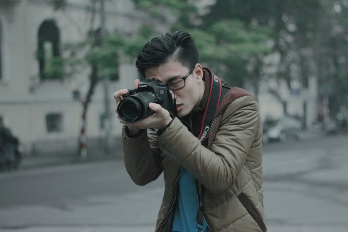 A photographer shooting with a canon DSLR on the street