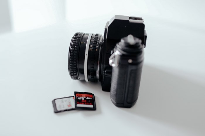 A camera on a white table with two memory cards beside