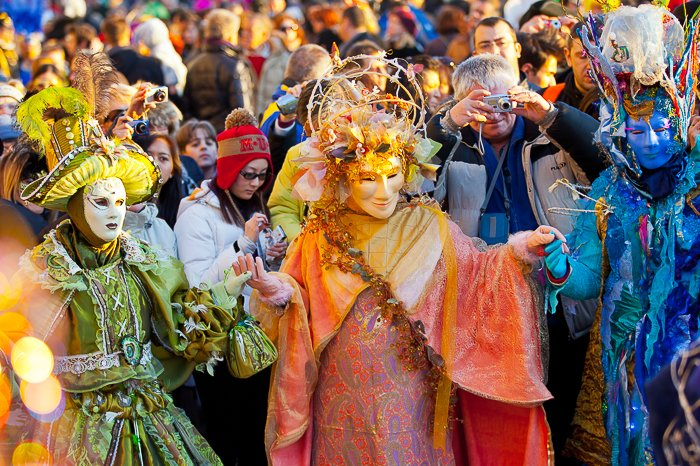 A group of three costumed carnival performers with a crowd behind
