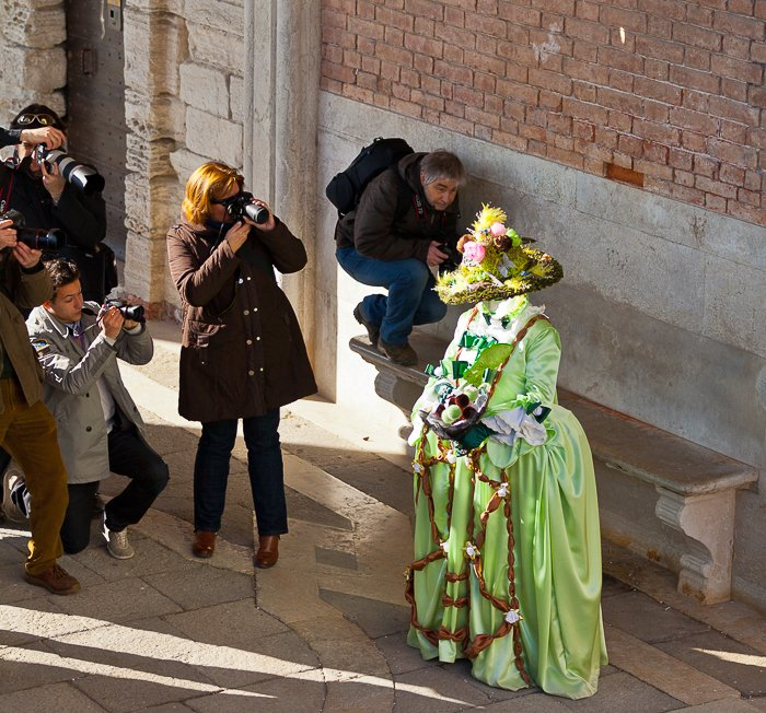 A crowd photographing a green costumed carnival exhibit