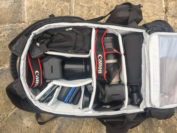 Overhead shot of a camera backpack with canon dslr and equipment inside