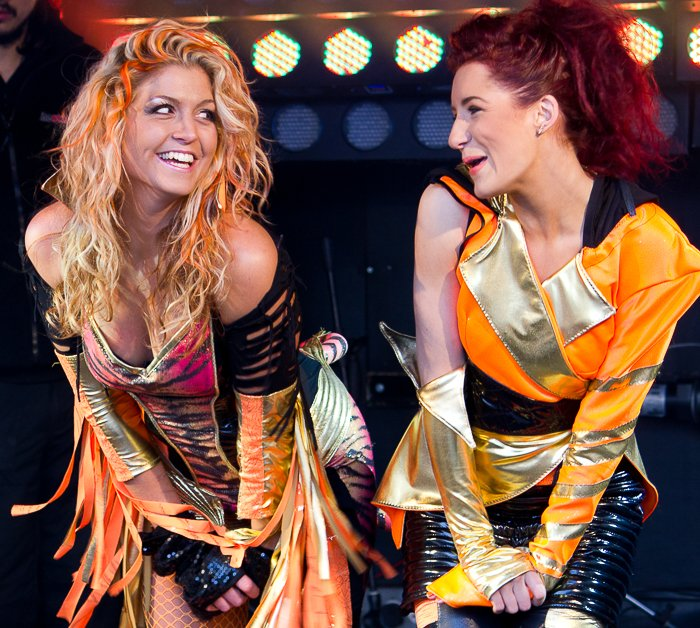 A carnival photography shot of two girls in costume smile at each other during a performance