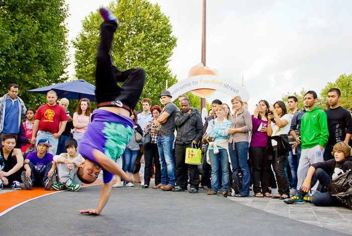 A guy break dancing at the Thames Festival with a crowd watching
