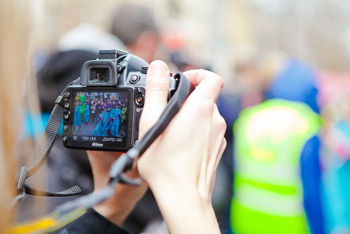 Close up of someone with a DSLR photographing a festival