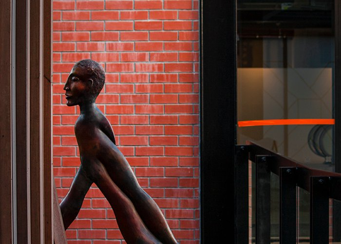 A bronze statue of a man by a red brick wall - color in photography