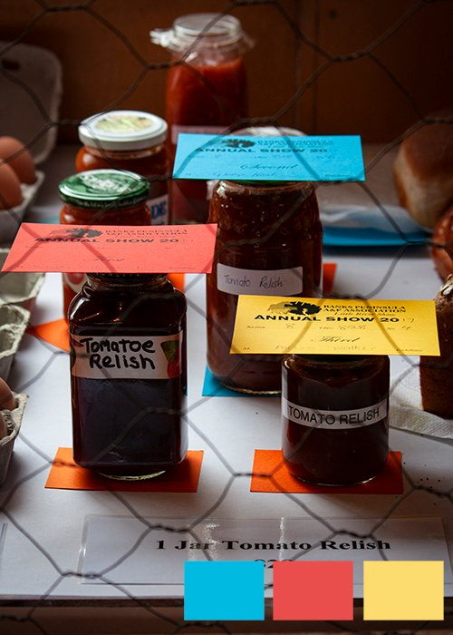 Jars of jam and relish with red, yellow and blue cards on the lids and squares of triadic color in photography examples in the lower right corner