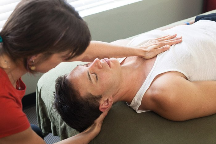 A business portrait of a woman giving a massage to a man lying on a table