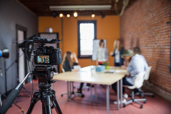 A commercial photography shoot set up with a dslr camera on tripod in the foreground, blurred background of people around a table