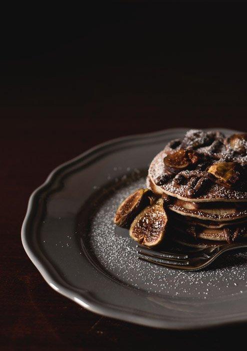 A dark photography still life setup of a luxurious dessert on a plate against a dark background