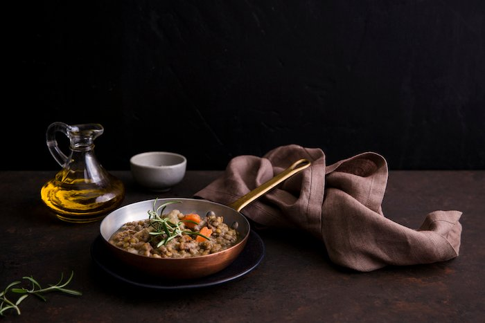 A dark food photography still-life setup of lentil soup in a copper pot on table