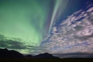 photo of the daytime sky merging into the northern lights
