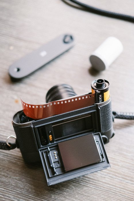 A film photography camera with roll of film on wooden table