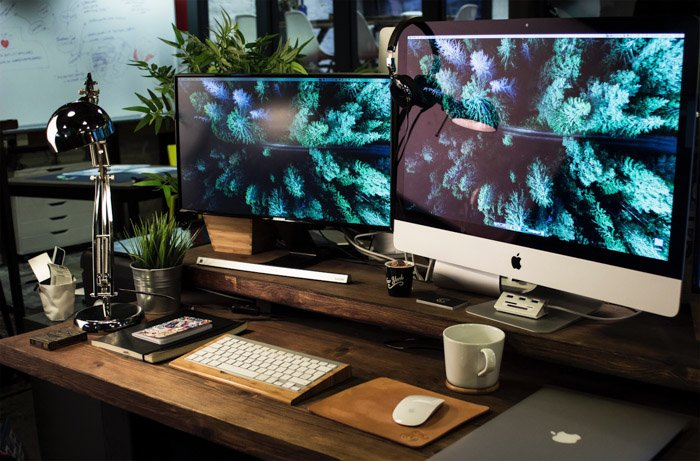 Two computers set up on a wooden desk in an office