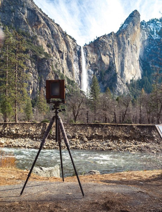 A tripod with film camera pointing towards a stunning mountainous landscape