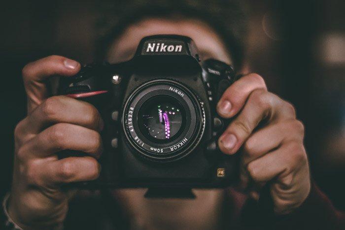 A person pointing a Nikon DSLR at the camera