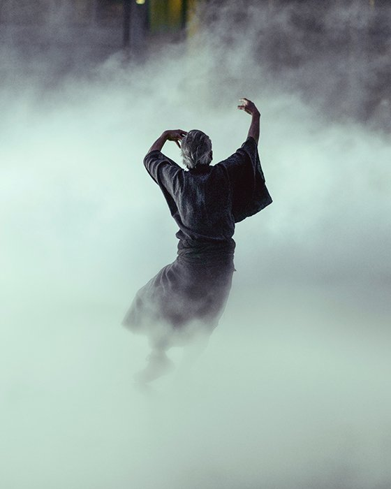 Atmospheric fine art photography portrait of a person dancing in the midst of smoke or fog