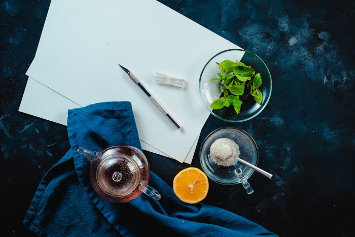 An overhead shot of paper, glassware, fruit and other food art props needed to create our final shot