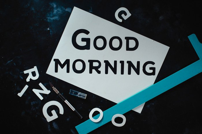 """Stencil made of white paper with the text """"Good morning"""" written on it, with additional white cutout letter and a paintbrush around the paper"""