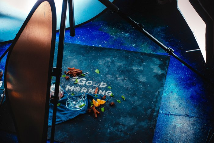 A behind the scene setup of shooting a food art still life with the words 'good morning' created with sugar, fruit and other food typography props