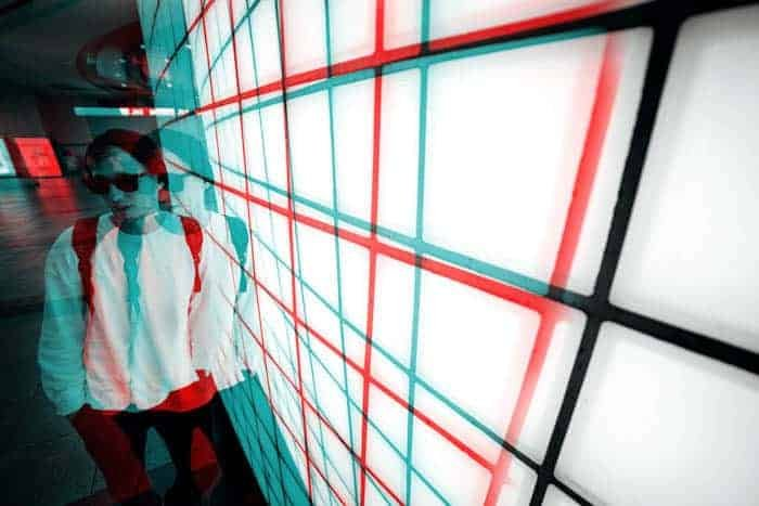 Cool glitch art portrait of a man leaning against a wall, coloured in teal, red, white and black