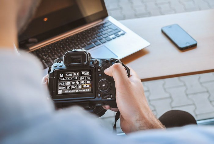 Close up of a male photographer holding a dslr camera and looking at the screen