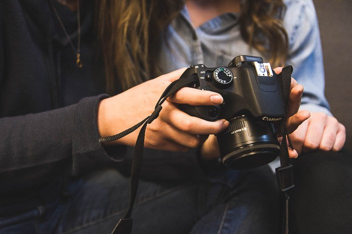 Close up of a girl holding a dslr camera and looking at the screen