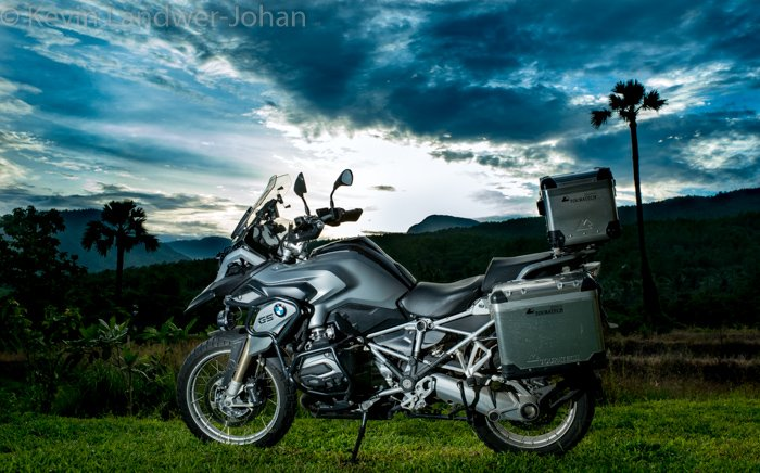 A silver motorbike with a stunning landscape behind and a watermark on top created in lightroom.