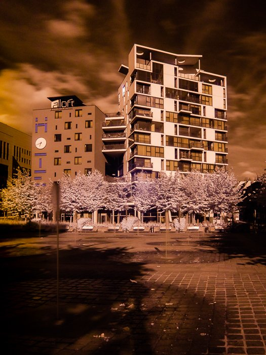 A false colour infrared image of the exterior of a large building using tones of orange.
