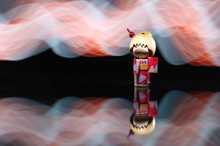 A Japanese wooden doll lit up using a smartphone's flashlight for light painting background