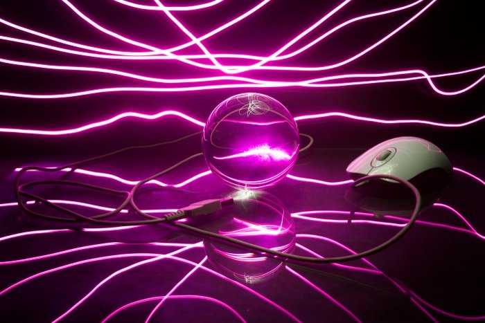 Atmospheric photo of a glass ball, computer mouse and cable surrounded by stunning purple light painting photography