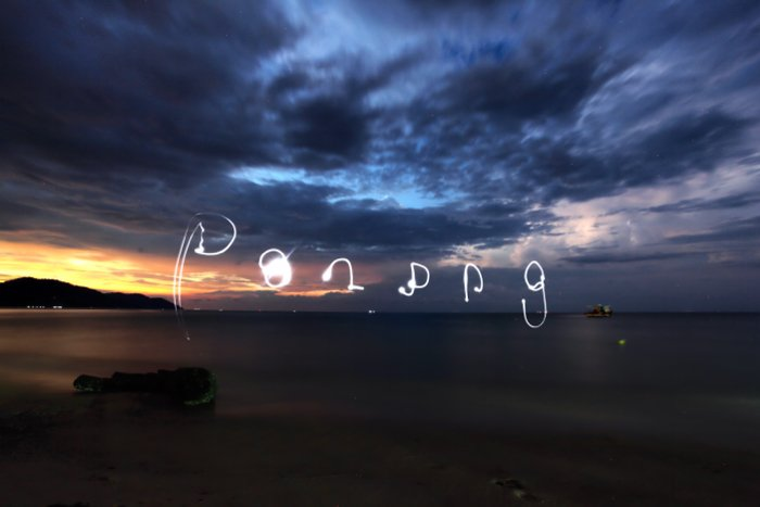 Words drawn in the sky over a seascape at night, using a smartphone's flashlight for light painting photography