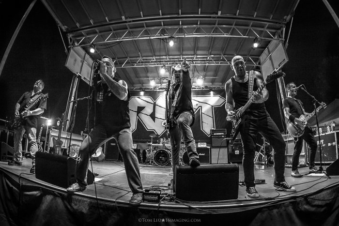 A black and white live music photography shot of a band onstage