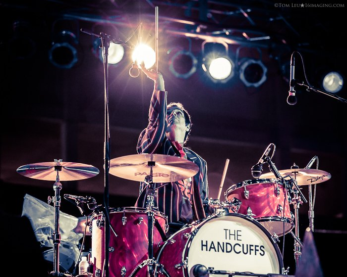 A music photography live shot of a drummer playing onstage