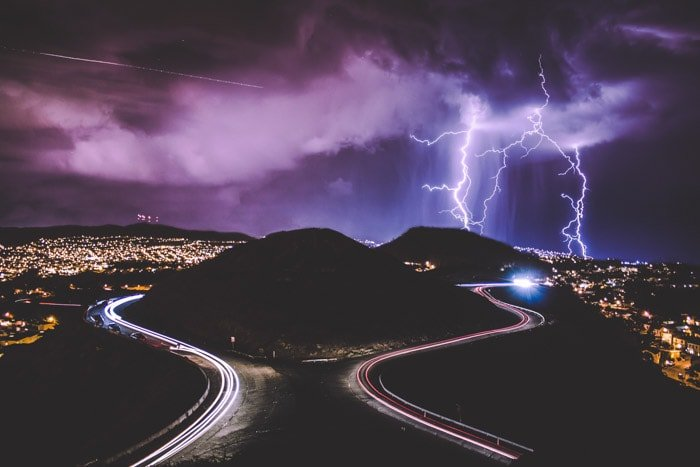 Magnificent overhead shot of a two roads with colored light trails bypassing a hill, fantastic purple skies and lightning striking above