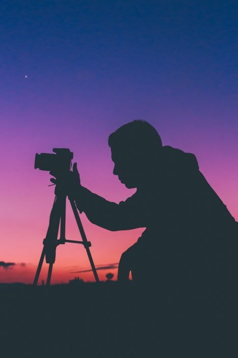 Night time silhouette of a photographer kneeling at his camera on a tripod with a brilliantly colored sky behind him