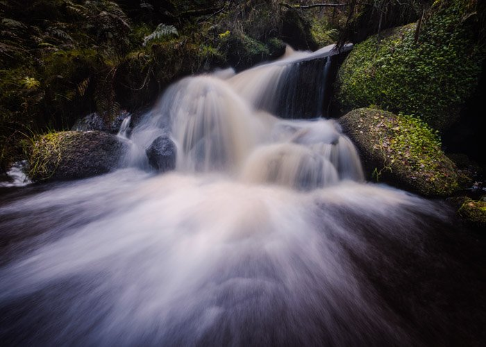 A waterfall with silky smooth flowing water over mossy rocks