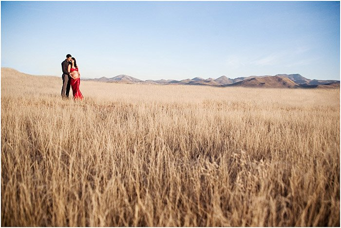 A couple pose together in calm cornfield landscape demonstrating maternity photography poses