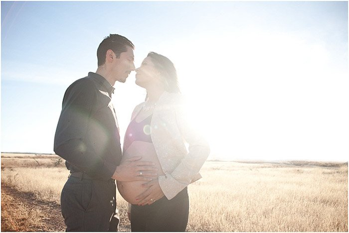 Dreamy maternity photo shoot of the father holding his wifes belly in cornfields